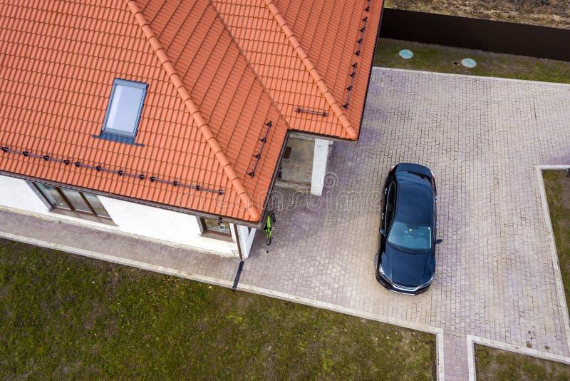 Lucht hoogste mening van de dakspaandak van het huismetaal met zoldervensters en zwarte auto op bedekte yard stock foto