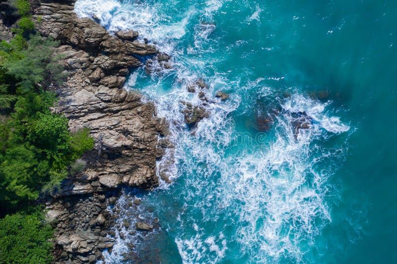 Lucht hoogste mening van de mooie golven die van de oceaan op de rotsachtige eilandkust verpletteren stock afbeeldingen