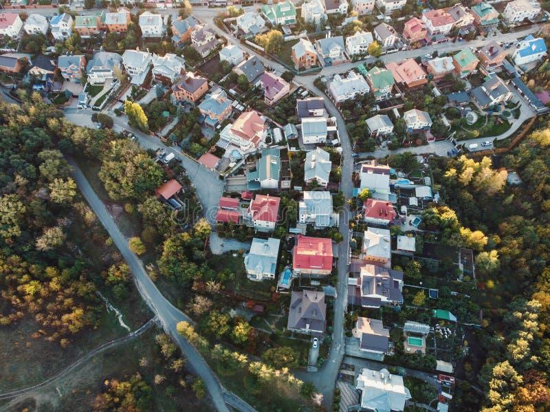 Lucht hoogste mening van vliegende hommel boven buurt in de voorsteden met woonhuizen en straten stock foto's