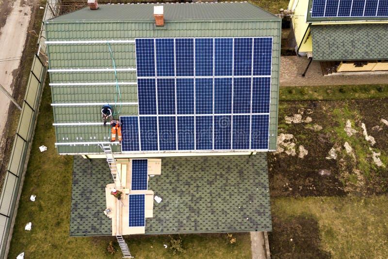 Lucht hoogste mening van woonhuis met team van arbeiders die het zonnesysteem van foto voltaic panelen installeren op dak Vernieu stock afbeeldingen