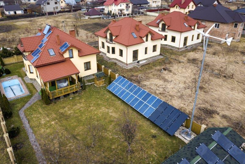 Lucht hoogste mening van woonwijk met nieuwe huizen met voltaic panelen van de dak de zonnefoto, de molen van de windturbine en z royalty-vrije stock afbeeldingen