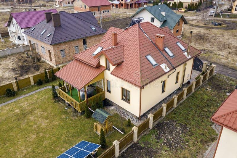 Lucht hoogste mening van woonwijk met nieuwe huizen met voltaic panelen van de dak de zonnefoto, de molen van de windturbine en z stock afbeeldingen