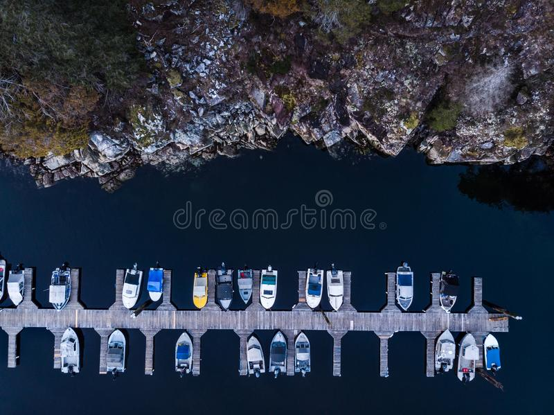 Lucht luchtmening van een houten bootdok naast een rotsachtige kustklip stock afbeeldingen