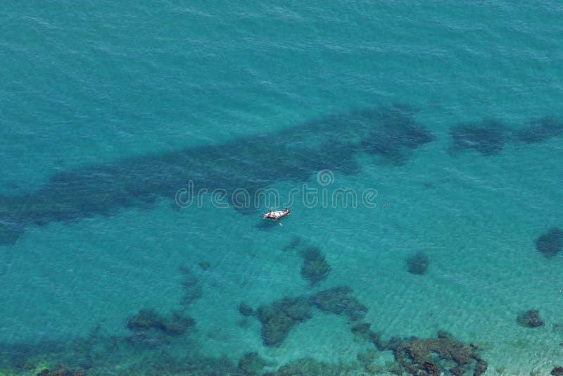 Lucht mening van duidelijk blauw water en gele boot stock foto