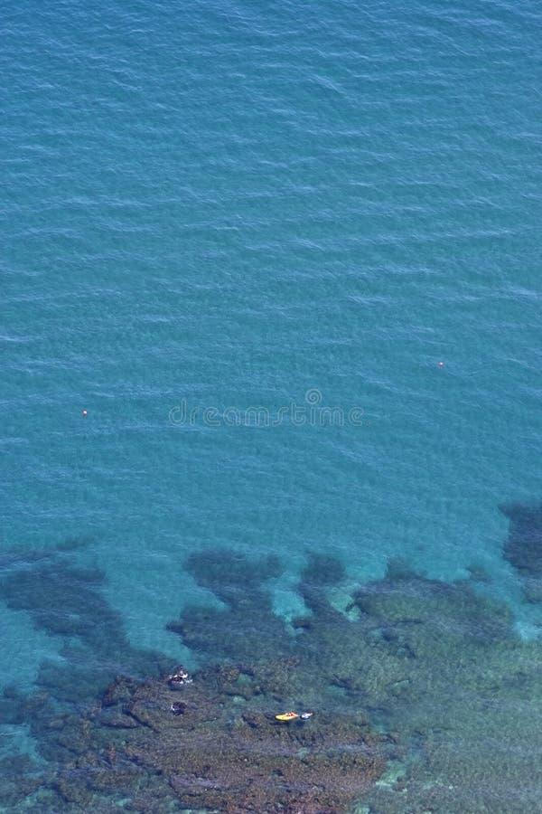 Lucht mening van duidelijk blauw water en gele boot stock afbeelding