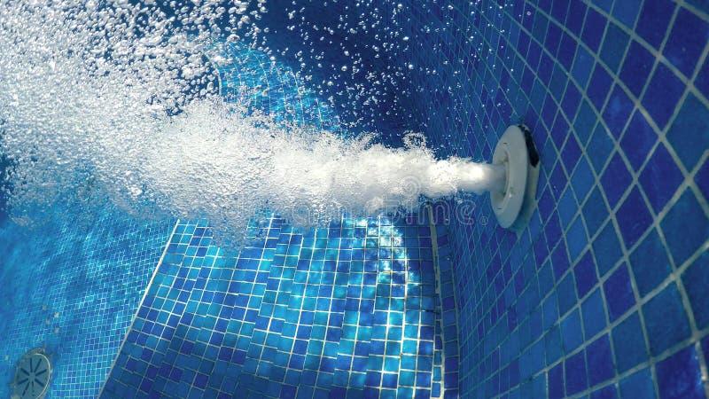 Luchtbellen van Jacuzzistraal in bruisend blauw water in een thermische kuuroordpool royalty-vrije stock afbeeldingen
