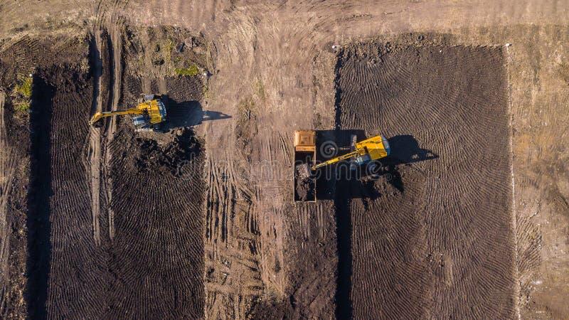 Luchtbouw - top down mening van een graafwerktuig en een vrachtwagen die aan een bouwwerf werken stock afbeeldingen