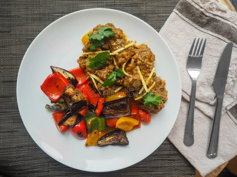 Luchtdieclose-up van het gekookt voedsel van het Middenoosten op een witte plaat met een vork en een keukenmes wordt geschoten royalty-vrije stock fotografie