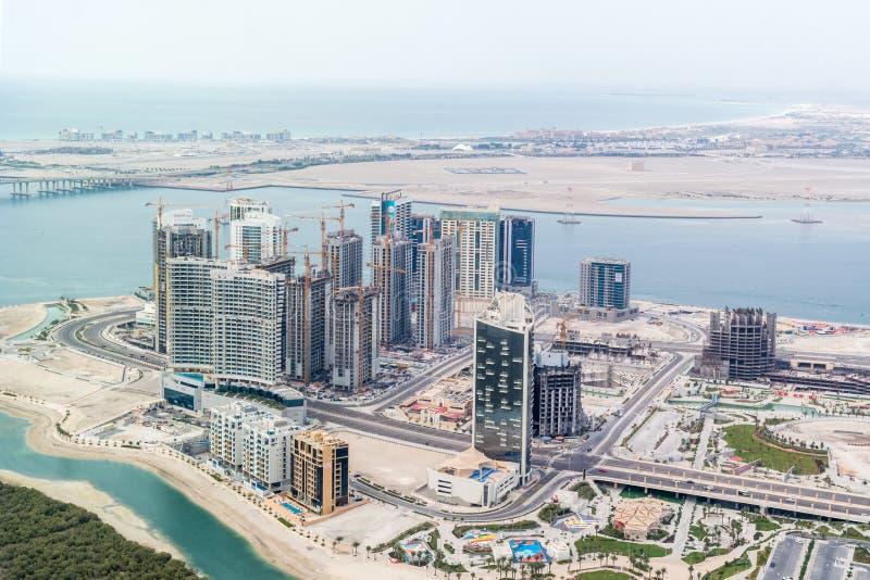 Luchtdiehommel van torens en wolkenkrabbers in aanbouw rond het overzees wordt geschoten - Al Reem Island, Abu Dhabi royalty-vrije stock afbeelding