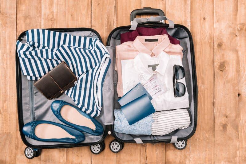 Luchtdiemening van reizigers` s toebehoren en kleren in open bagage worden georganiseerd royalty-vrije stock foto's