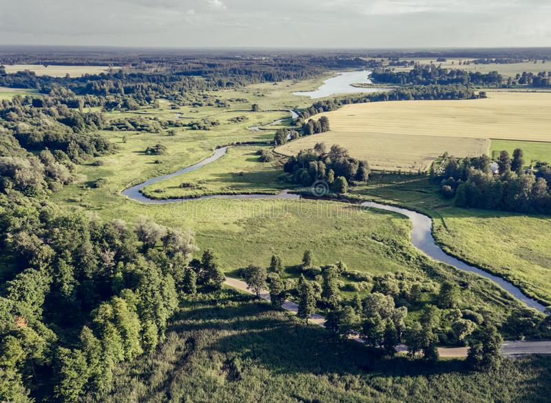 Luchtfoto de Rivier die tussen Gele en Groene Landbouwgebieden stromen in de Vroege Lente op Sunny Day - Concept het Vreedzame Le royalty-vrije stock fotografie