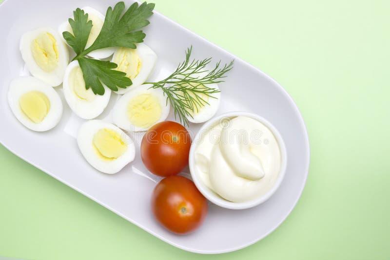 Luchtfoto van plantaardige salade met gekookt kwartelsei, dille, verse tomaat en sla op witte porseleinplaat Een gediende salade  stock fotografie
