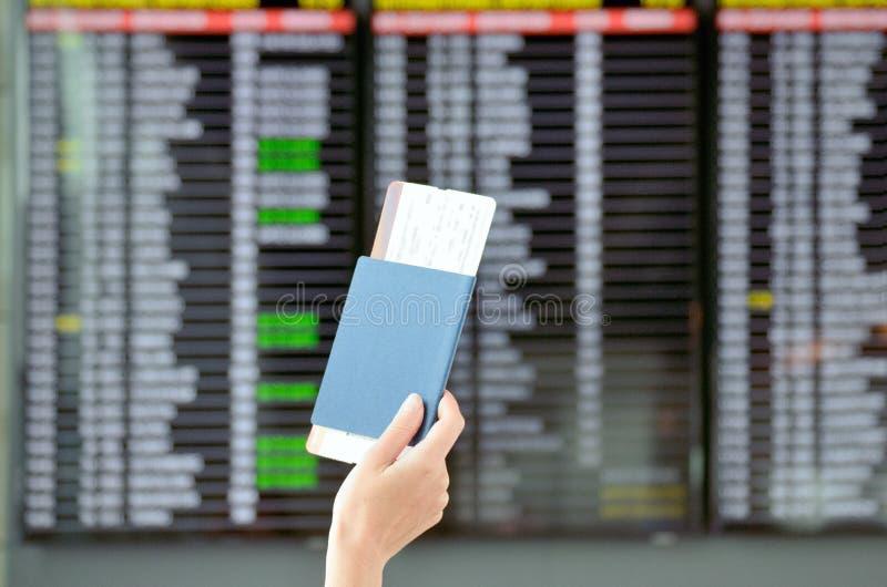 Luchthaven en reisconcept, hand met paspoort en vluchtkaartjes met tijdschemaachtergrond stock foto