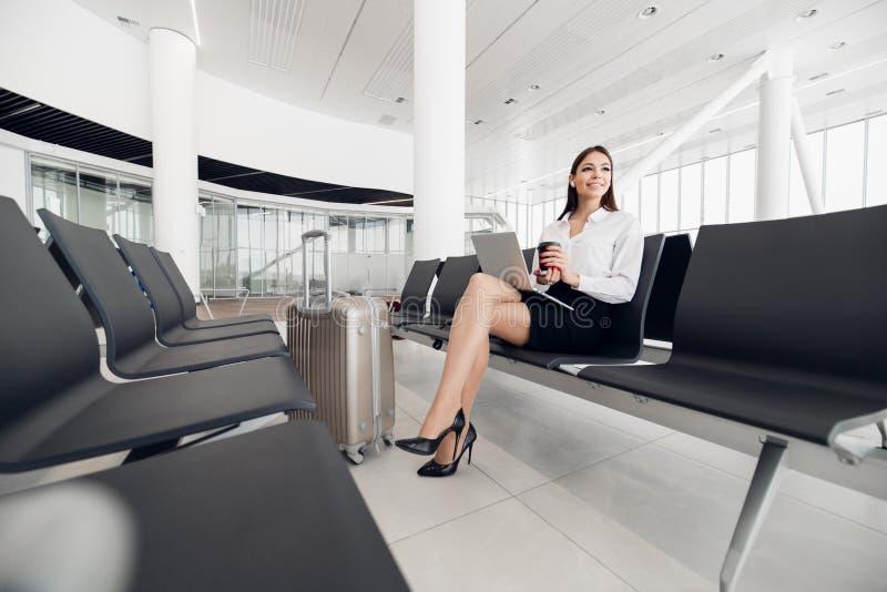 Luchthaven Jonge vrouwelijke passagier op slimme telefoon en laptop zitting in eindzaal terwijl het wachten op haar vlucht lucht royalty-vrije stock fotografie