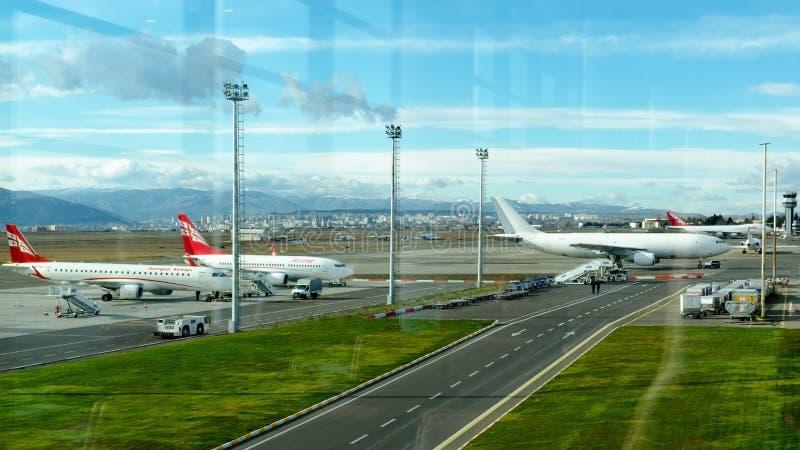 Luchthaven met de luchtroutes van vliegtuigenairzena en andere vliegtuigen die zich in parkeerterrein bevinden stock afbeeldingen
