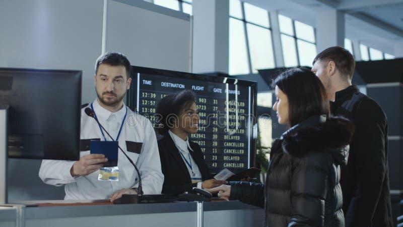 Luchthavenarbeiders die documenten controleren op controlepunt stock fotografie