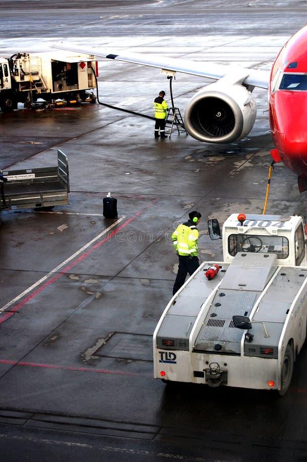 Luchthavenarbeiders die het vliegtuig klaar krijgen op tijd op te stijgen stock afbeeldingen