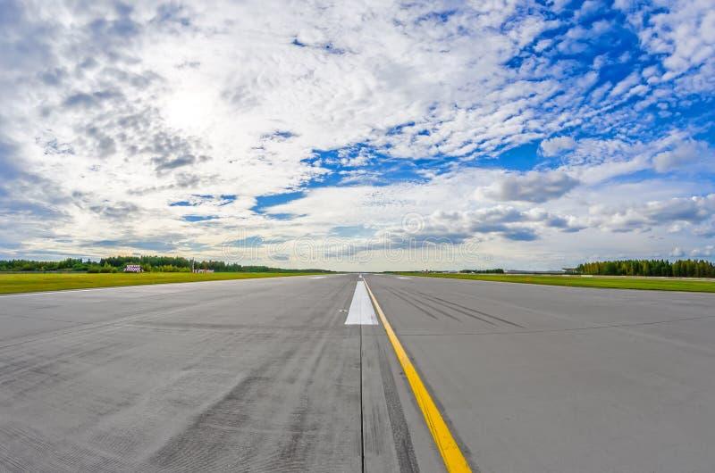 Luchthavenbaan aan in horizon en schilderachtige wolken in de blauwe hemel stock foto's