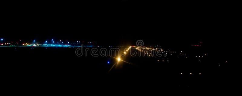 Luchthavenbaan door heldere het landen lichten bij nacht wordt verlicht die stock foto