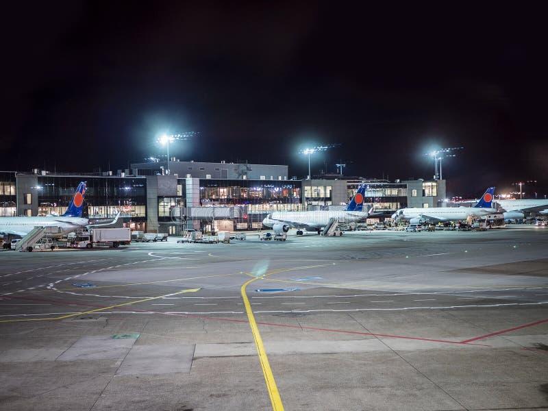 Luchthavenbaan met sommige vliegtuigen, bij nacht stock afbeeldingen