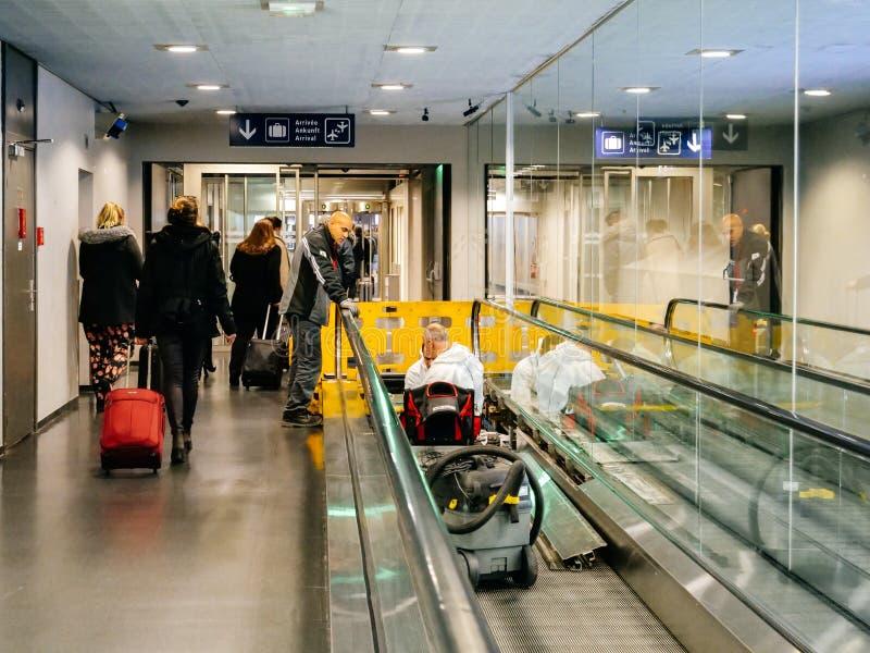 Luchthavenscène met arbeiders van Schindler-rollend trottoir stock foto's