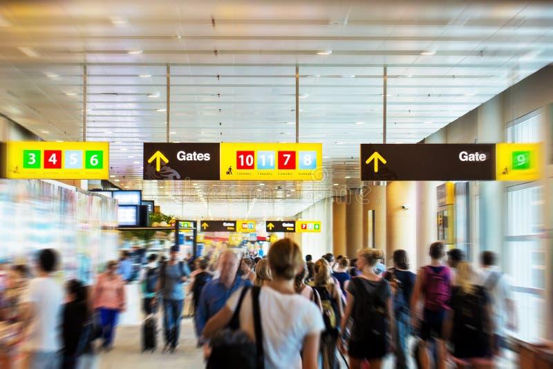 Luchthaventerminal met mensen hurrieng aan de poorten stock fotografie
