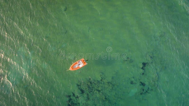 Luchthommelmening van mooie schone wateren in Korfu Griekenland en een geïsoleerde oranje boot De ruimte van het exemplaar stock foto