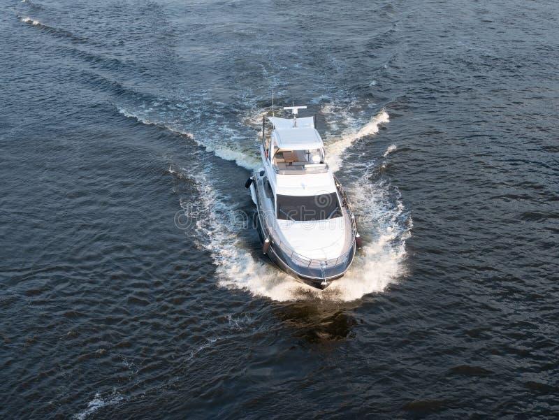 Luchthommelschot van klein gemotoriseerd wit jacht die bij het overzees varen stock afbeelding
