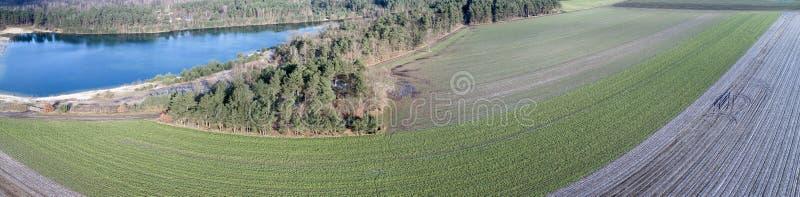 Luchtlandschapsmening, luchtfoto met een meer, gebieden, weiden, bossen en een weg, panorama als banner voor een blog of website stock afbeeldingen