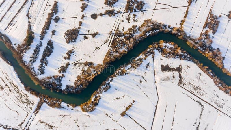 Luchtmening die riverbend sneeuw behandelde gebieden overgaan royalty-vrije stock fotografie