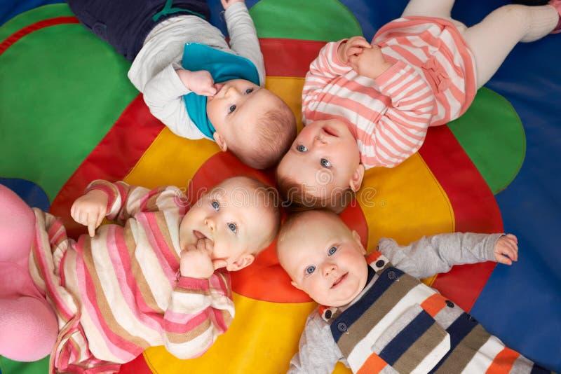 Luchtmening die van Babys op Mat At Playgroup liggen stock afbeeldingen
