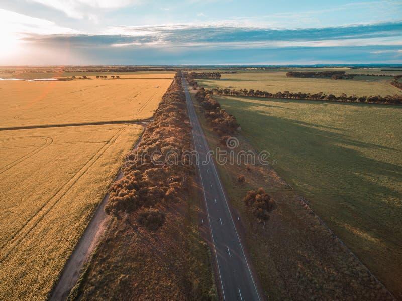 Luchtmening die van landelijke weg door landbouwgrond in Australisch platteland bij zonsondergang overgaan royalty-vrije stock foto