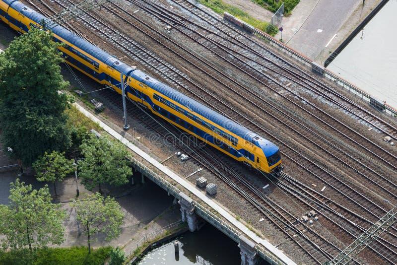 Luchtmening die van Nederlandse trein een brug over een kanaal kruisen stock foto's