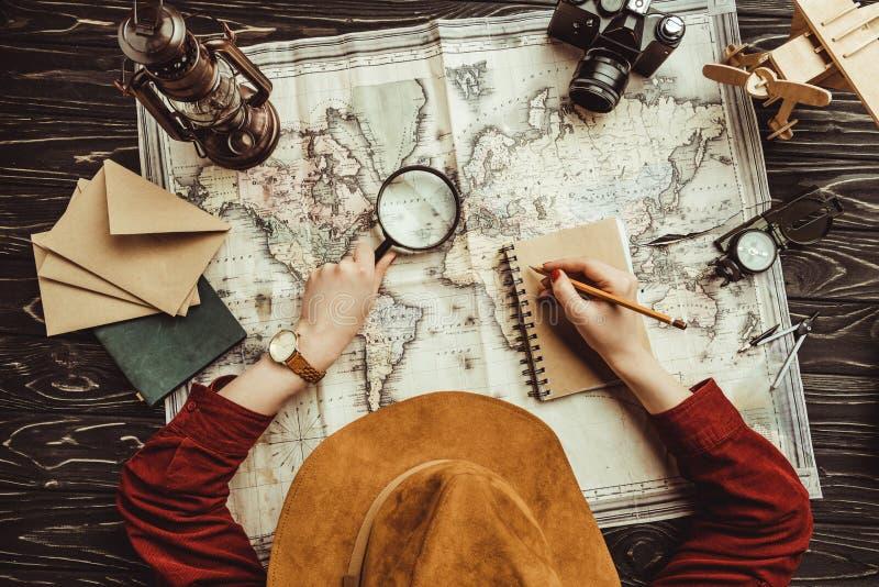 luchtmening die van vrouw nota's in notitieboekje met lege enveloppen, kaart en fotocamera maken stock foto's