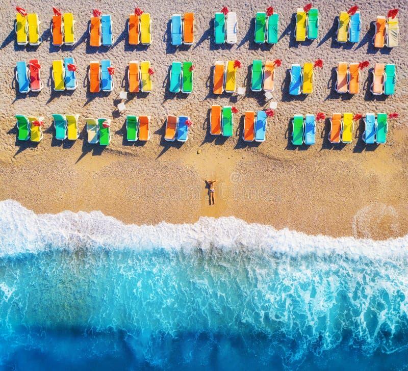 Luchtmening die van vrouw op het strand met kleurrijke chaise-zitkamers liggen stock afbeelding