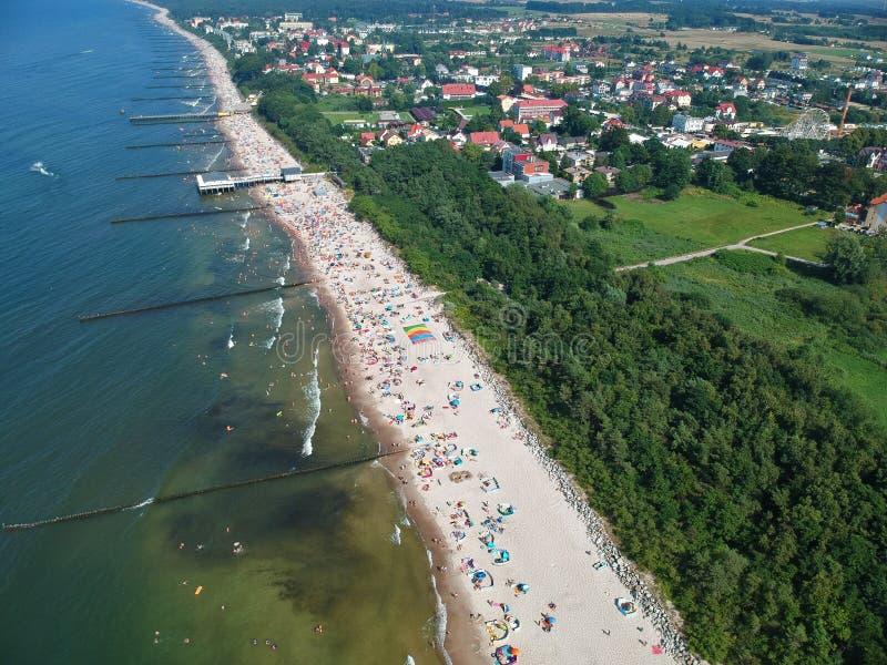 Luchtmening over een overzees met golfbrekers, strand, bomen en kleine stad royalty-vrije stock foto's