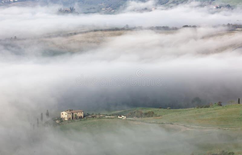 Luchtmening van de boerderijen van de heuveltop & cipresbomen in Toscanië op een mistige de lenteochtend ~ stock foto's