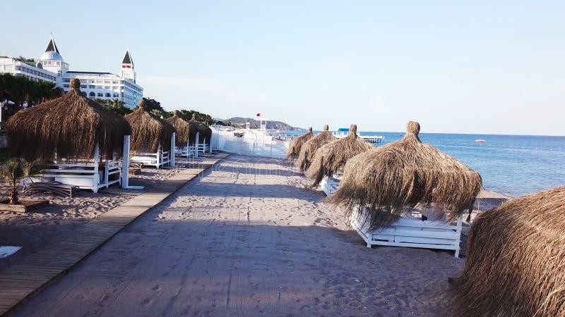 Luchtmening van de golven, zandig strand met rietparaplu's video Hoogste mening van het zandige strand met natuurlijke umbrelas royalty-vrije stock fotografie