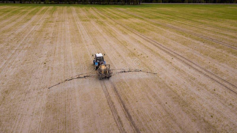 Luchtmening van de landbouw van tractor die en op gebied ploegen bespuiten stock foto's