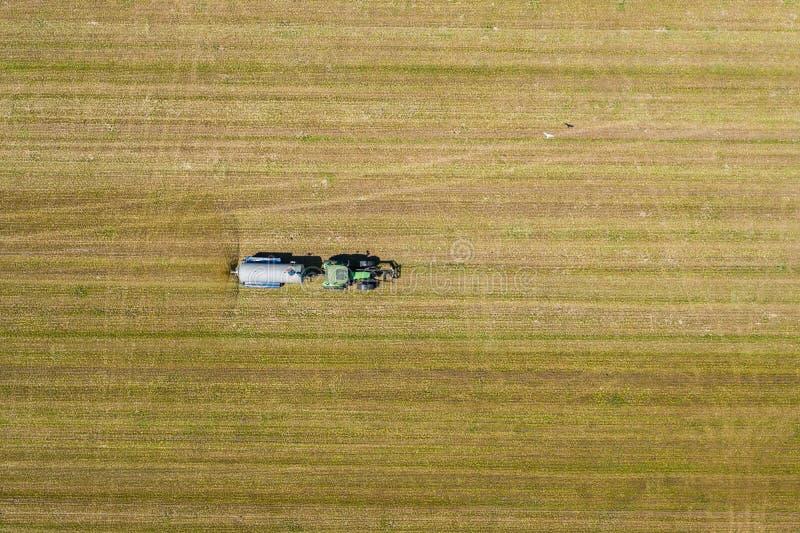 Luchtmening van de landbouw van tractor die en op gebied ploegen bespuiten Landbouw Mening van hierboven Foto met hommel wordt ge royalty-vrije stock foto
