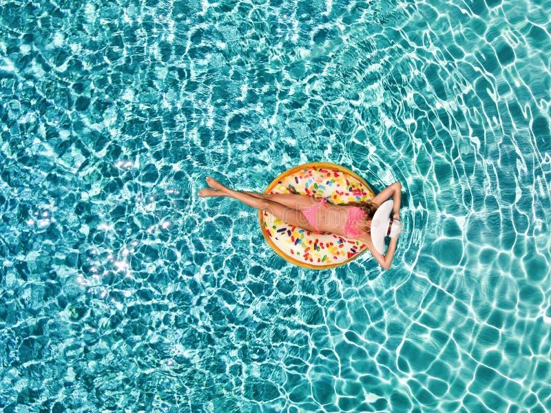 Luchtmening van een aantrekkelijk meisje die over turkooise wateren op een doughnut gevormde vlotter drijven royalty-vrije stock afbeeldingen