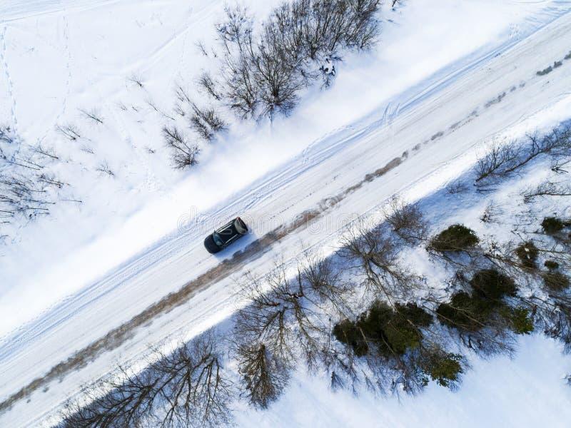 Luchtmening van een auto op de winterweg Het platteland van het de winterlandschap Luchtfotografie van sneeuwbos met een auto op  stock fotografie