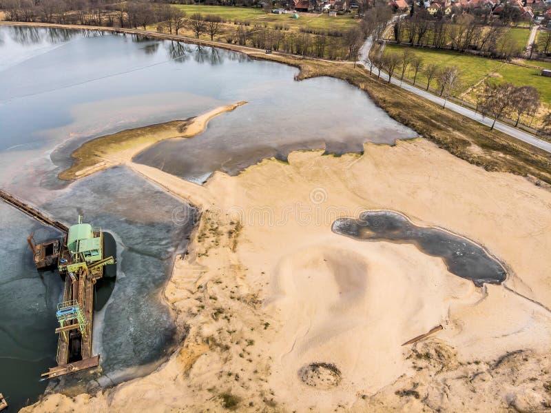 Luchtmening van een gebied van de zandmijnbouw en het bijbehorende uitgravingsmeer stock foto