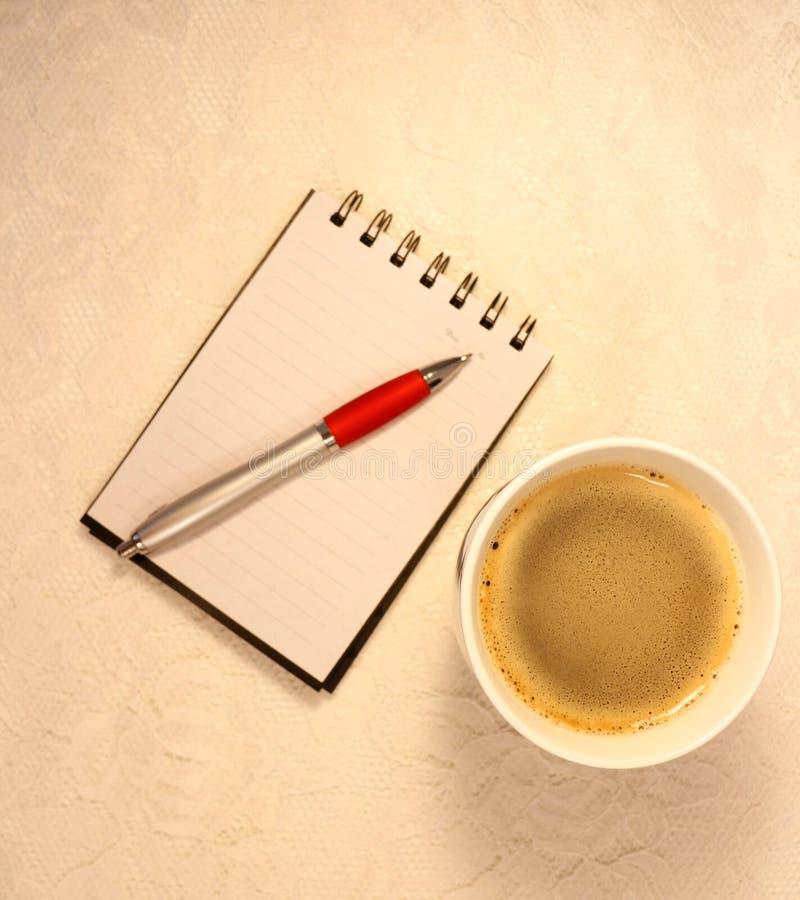 Luchtmening van een kop van koffie, notitieboekje en een inktpotlood stock foto