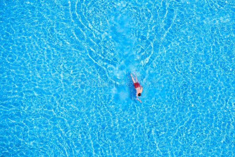 Luchtmening van een mens die in de pool zwemmen stock afbeeldingen