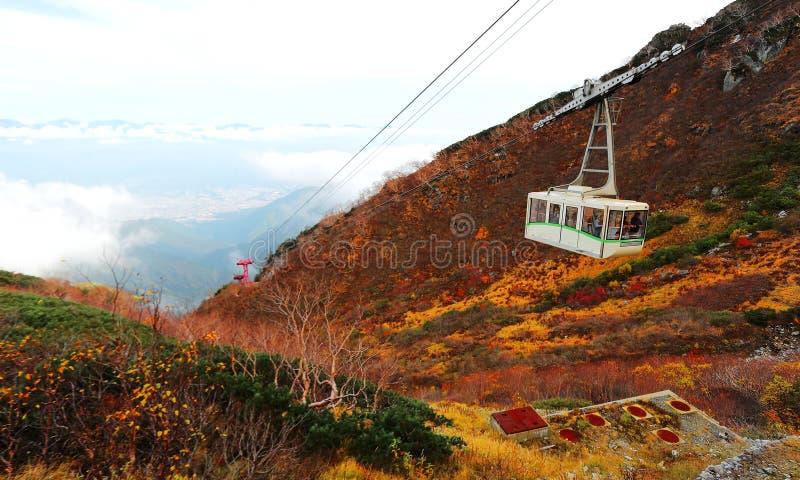 Luchtmening van een toneelkabelwagen die over de wolken tot de de herfstbergen glijden in het Japanse Centrale Nationale Park van royalty-vrije stock fotografie
