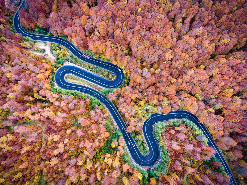 Luchtmening van een windende weg in de bergen in de herfstseizoen stock foto