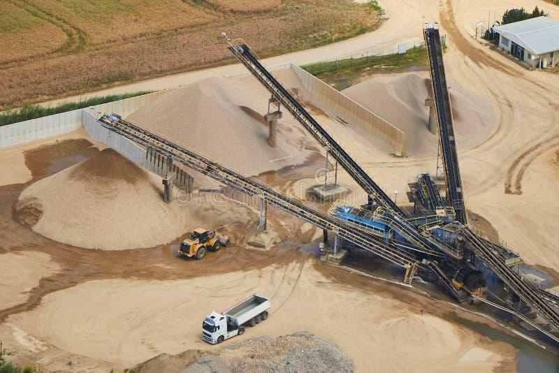 Luchtmening van een zandfabriek met stapels van zand en zware machines stock afbeelding