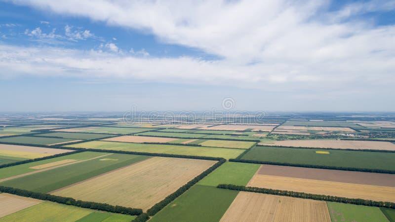 Luchtmening van gebieden met diverse soorten landbouw, tegen bewolkte hemel stock foto's