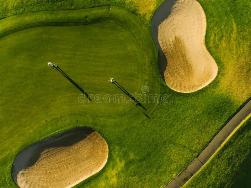 Luchtmening van golfspelers bij groen zetten stock foto's